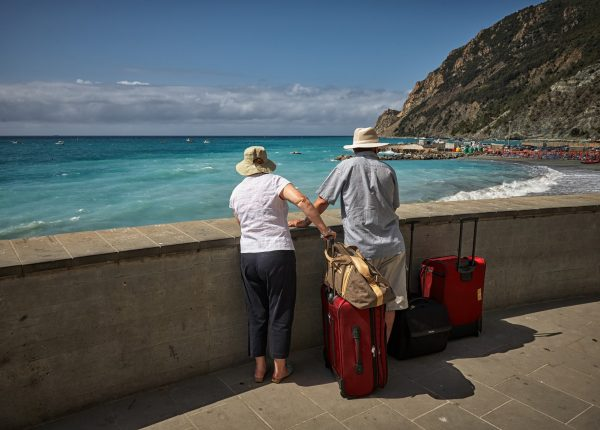 old couple with suitcases by beach