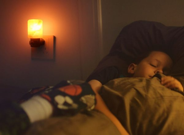 a boy sleeping on a cozy bed in a dimly lit room