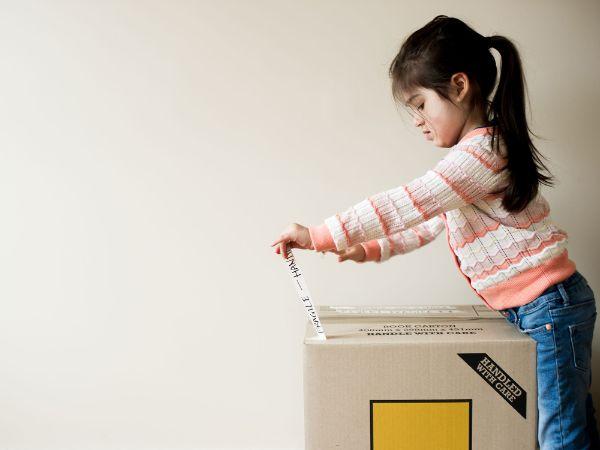 a little girl opening a box
