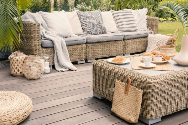 patio set with beige cushions standing on a wooden board deck. Breakfast on a table on a backyard porch.