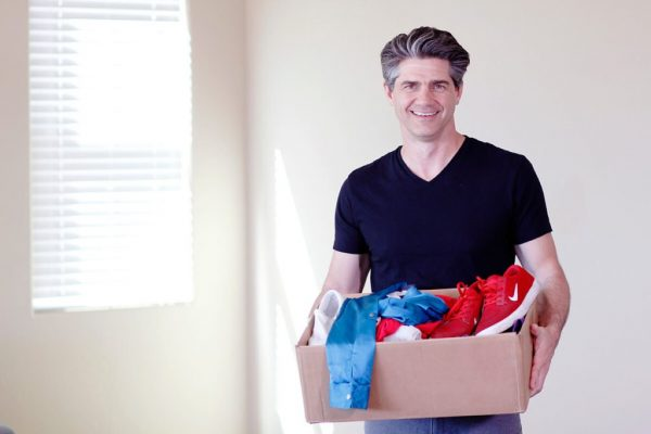 a man carrying a box of clothes to donate while he declutters
