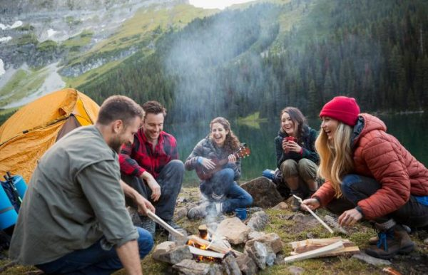a group of friends enjoying a camp fire by the lake
