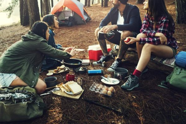 a group of friends preparing food while camping in the woods