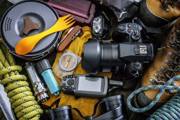 close up view of travel equipment and accessories for mountain hiking trip on wood floor.