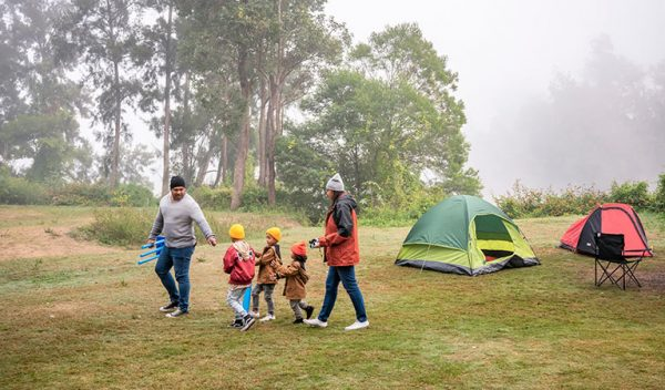 a young family walking around their camp site