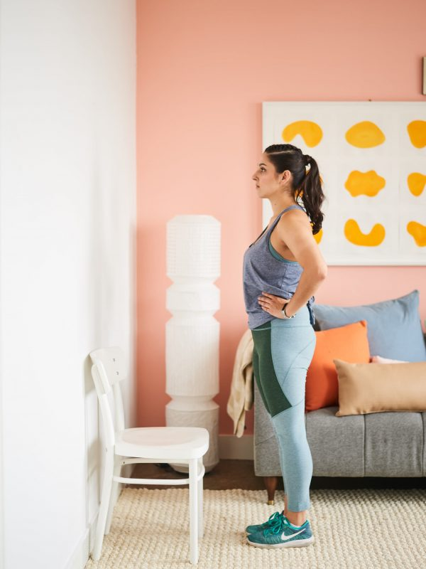 a woman doing step-ups in her room using a wooden chair