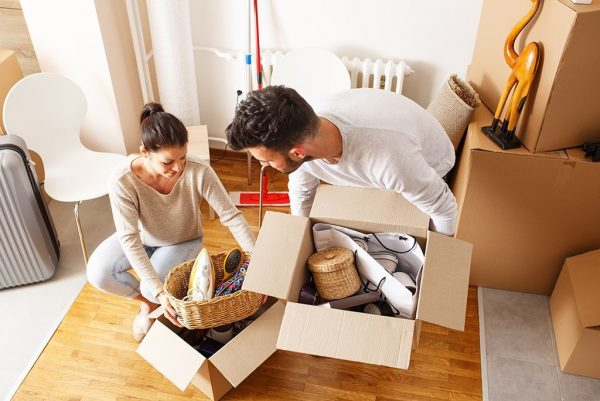 young couple unpacking cardboard boxes at new home