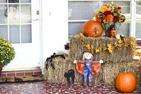 pumpkin and hay decorated on a porch for fall