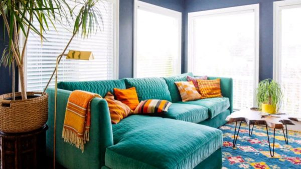 a vibrant blue green couch with brown throw pillows in a livingroom