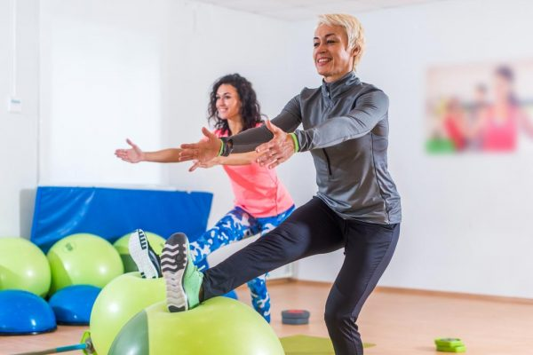 two friends doing single leg squats using yoga balls