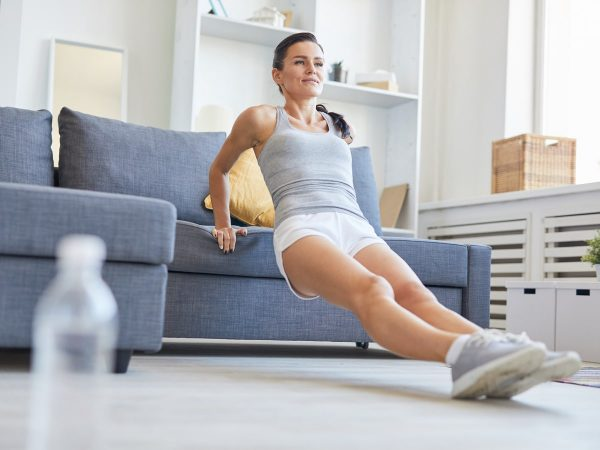 a woman doing couch dips from her living room