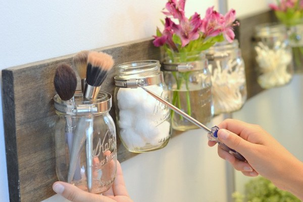 a woman screwing the mason jars to the wall using a screw driver