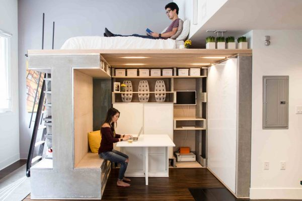 a man reading a book on his loft type bed while his girlfriend is working below it