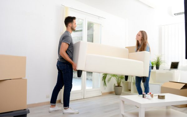 a young couple moving a small couch