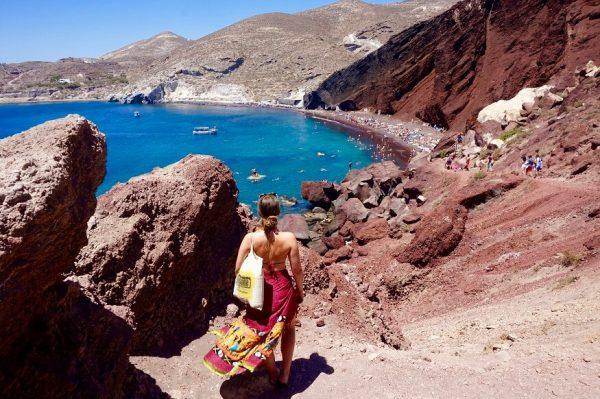 a woman in a beach dress looking at the beach at red beach santorini