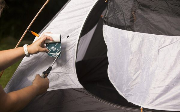 a man covering the hole on his tent with a tape