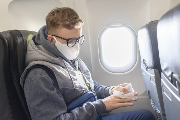 a man on a plane wearing a surgical mask while wiping his hands with wet wipes