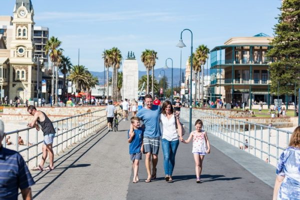 a mom, dad and their kids walking to the beach in glenelg