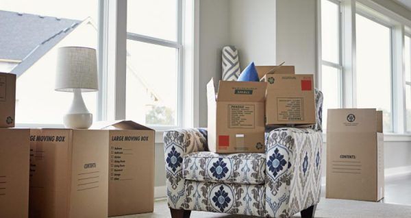 stacks of cardboard boxes and a small couch in an empty room