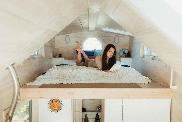 a woman reading a book on her loft bed