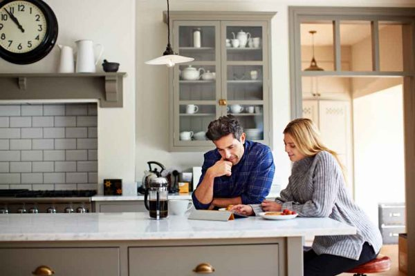 a couple having breakfast in the kitchen while reading the news on their tablet