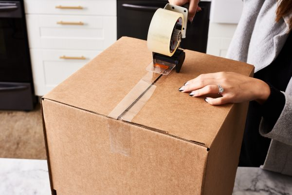 a person sealing a box with tape