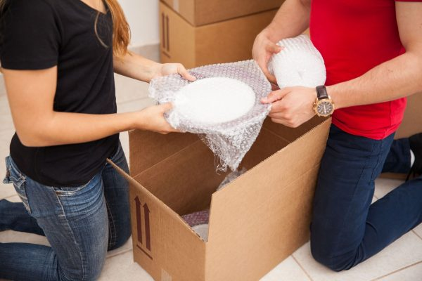 two people wrapping bubble wrap on plates and storing them in cardboard boxes