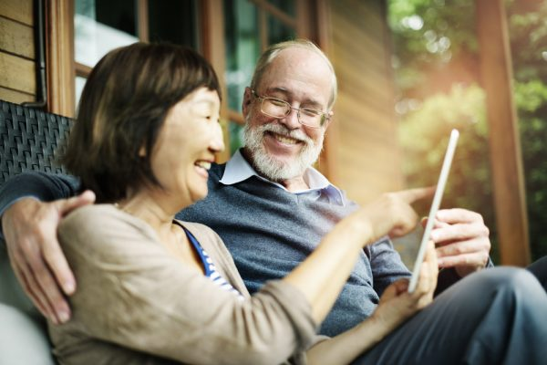 a happy retired couple using a tablet