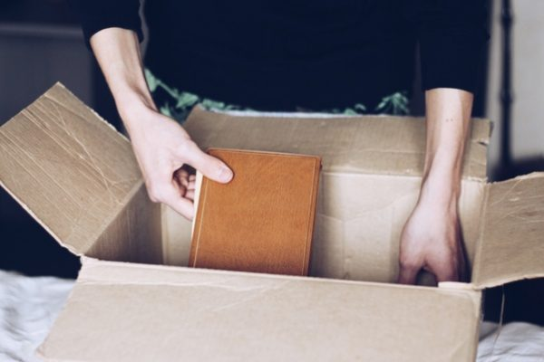 a woman placing a book inside a cardboard box