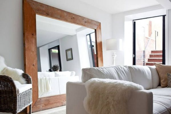 A big tall mirror with wooden frame placed behind a sofa