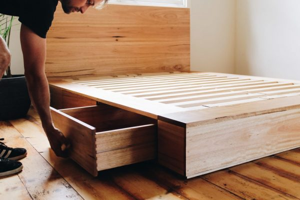 A man pulling a drawer open under the bed