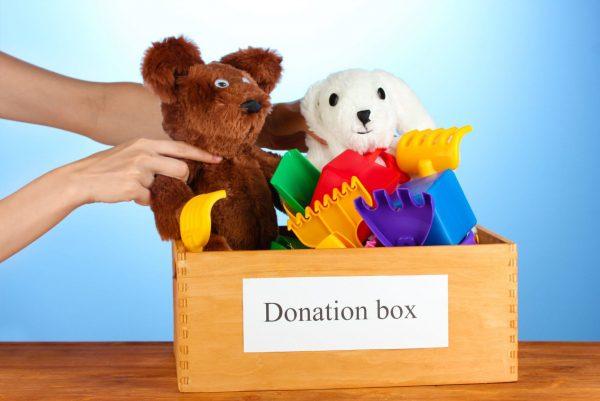 A person placing a stuffed teddy bear in a cardboard box