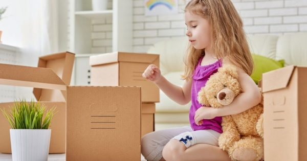 A girl holding her teddy bear while looking into the cardboard box