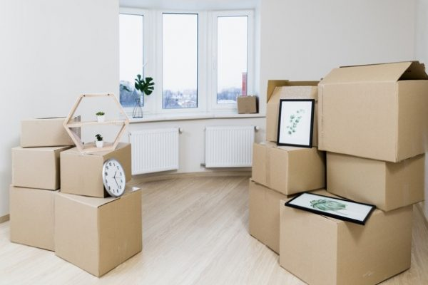 Cardboard boxes stacked up together in an empty living room apartment