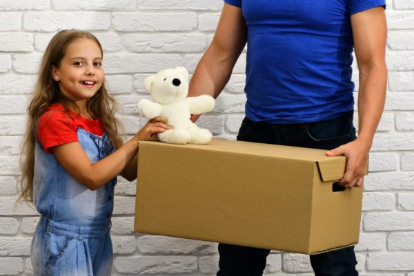 A girl holding a stuffed white teddy bear next to a man carrying a cardboard box