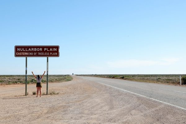A woman standing under a big signage at Nullarbor