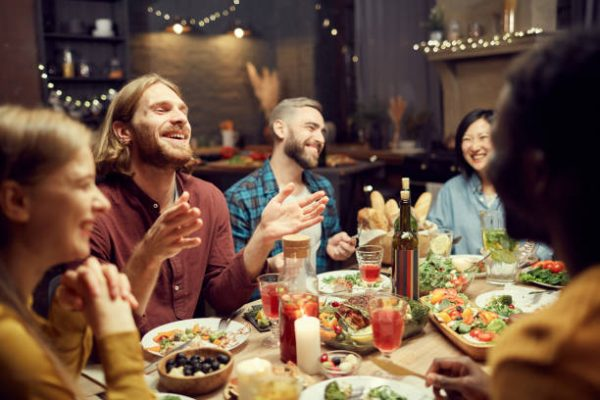 Group of friends enjoying dinner party with friends and smiling happily sitting at table in dimly lit room