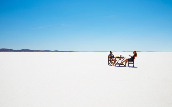 A couple enjoying wine under the heat of the sun in Lake Eyre