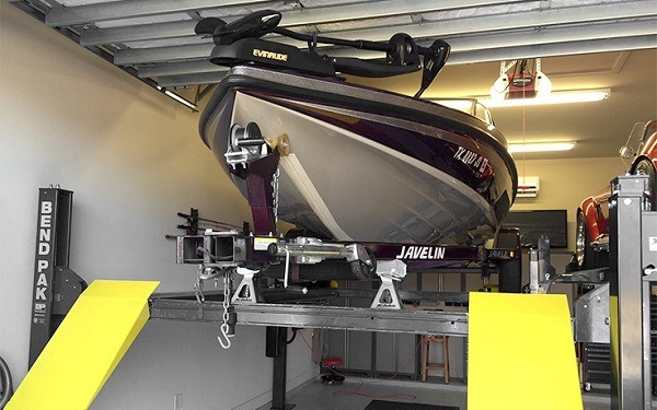 A boat parked on a lift inside a garage