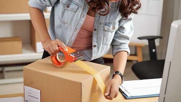 A woman sealing a cardboard box with tape