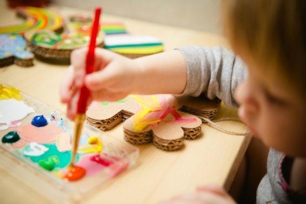 A kid painting on cardboard cutouts