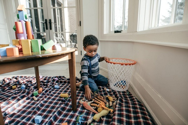 A toddler putting his toys in the basket
