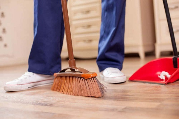 A person sweeping the floor with a broom