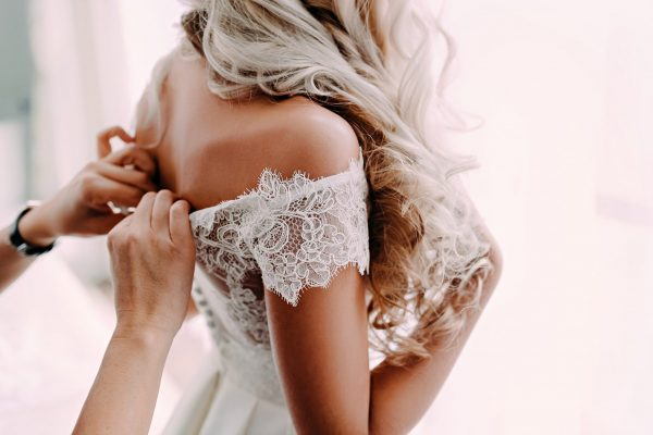 Woman getting dressed with a wedding dress
