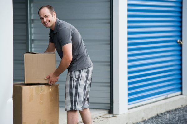 A man carrying boxes inside the storage unit
